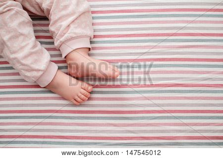 baby leg on the striped background. the view from the top. on a bed at home