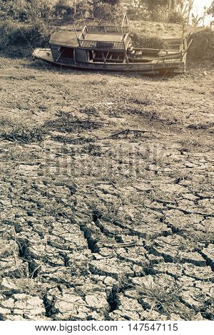Dried river with old boat on cracked earth fissure sepia warm tone