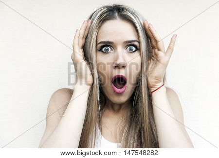 Portrait of the young scared girl on a light background.