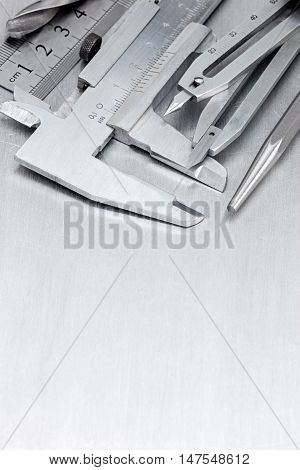 Vernier Caliper, Ruler, Compass And Other Tools On Scratched Metal Background