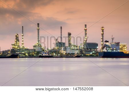 Oil refinery river front with twilight sky during sunrise
