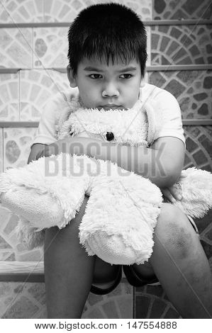 little boy sitting alone at staircase in the parkblack and white tone