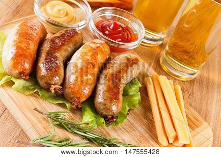 Oktoberfest beer traditional menu, grilled sausage with ketchup, mustard and rosemary. Wooden cutting board