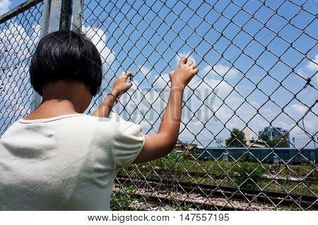 asian girl sad alone hand hold jail at Railroadrailway station