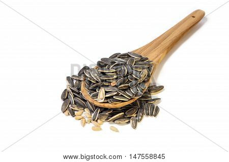 Roasted Sunflower Seeds in shell and shelled on a wooden spoon isolated on white background.