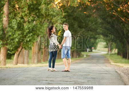 backside of young couple walk on country road outdoor, romantic people concept, summer season