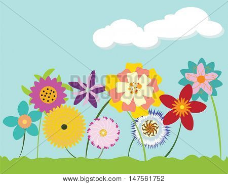 Bright multi-colored flowers sprouting up from grass against cloudy blue sky