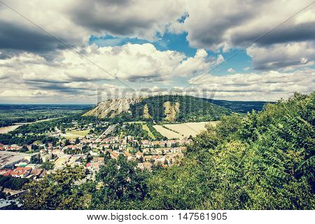 Braunsberg hill and Hainburg an der Donau Austria. Blue photo filter. Cloudy sky and greenery.