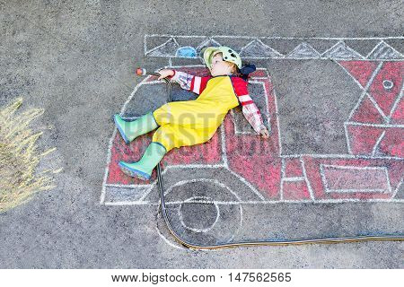 Creative leisure for kids: adorable toddler child  having fun with fire truck picture drawing with chalk, outdoors. Dreaming of future profession.