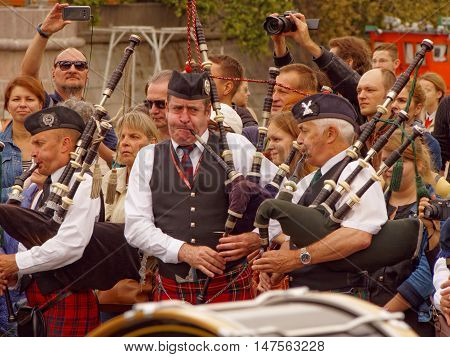 MOSCOW, RUSSIA - September 4, 2016: Bagpipers of Celtic pipes and drums band surrounded by townspeople in the Park of arts