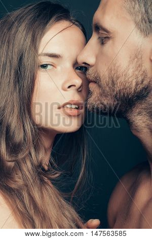 young sexy couple of woman or girl with pretty face and long hair embrace handsome muscular unshaven man