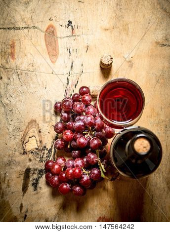 Bunch of red grapes with a bottle of wine. On wooden background.