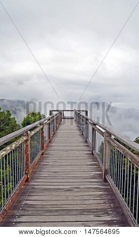 Wooden walkway bridge leading into low cloud above mountains in Dorrigo National Park, New South Wales, Australia