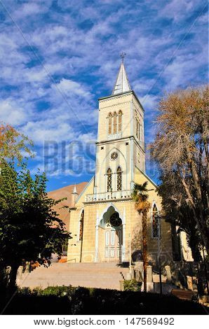 Low angle view of the church in Pisco Elqui with trees on eather side and a blue sky with some white clouds in the Elqui Valley in Chile, South America