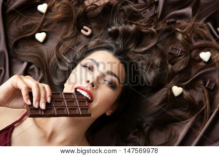 Beautiful girl eating chocolate on brown background