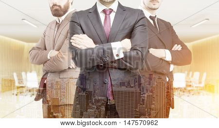 Three business partners in suits standing in office meeting room with arms folded. City panorama at foreground. Concept of profitable business. Toned image. Double exposure