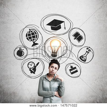 Portrait of African American girl standing near concrete wall with light bulb and education icons drawn on it. Concept of choosing the right university for you