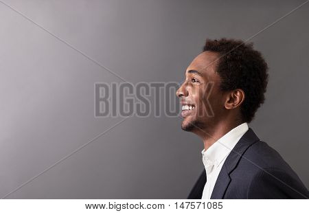 Portrait of happy African American businessman in suit standing against gradient gray background and smiling broadly. Concept of success and luck in business