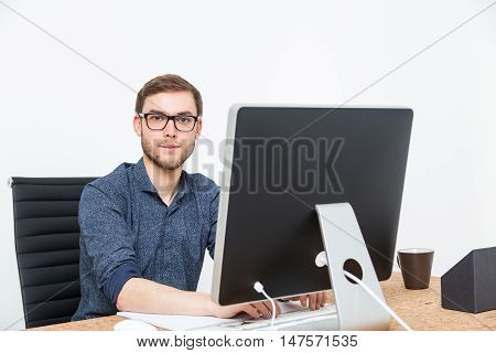 Businessman Looking To Camera At Table