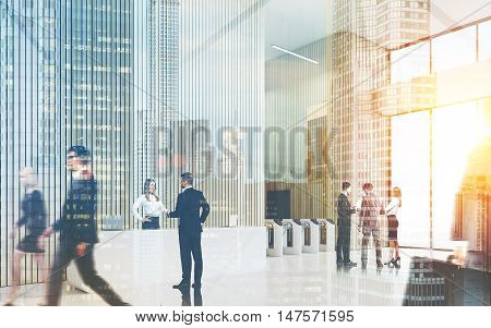 Busy office lobby. Man and woman are shaking hands. Their colleagues are discussing future board meeting. Concept of large company office. Toned image double exposure