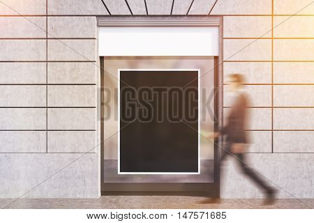 Businessman in glasses going past sunlit shop window with framed black poster. Concept of advertisement copyspace. 3d rendering. Mockup. Toned image