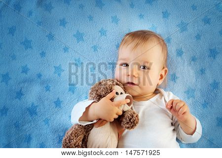 One year old baby lying in bed with a plush teddy bear