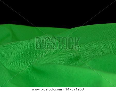 texture of green fabric, rich color laid in the crease on a black background