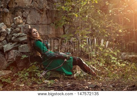 Elf Woman In Green Leather Armor With The Bow And Arrows Is Relaxing On The Rocks.