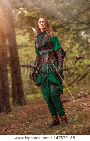 Elf Woman In Green Leather Armor With The Bow And Arrows On The Forest Background.