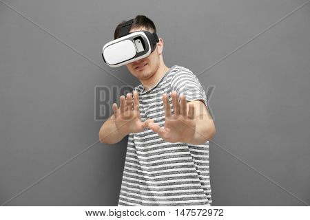 Young man in striped T-shirt wearing virtual reality glasses on grey background