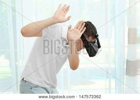 Young man wearing virtual reality glasses and standing near window in a room