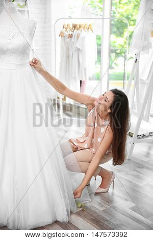Pretty young dressmaker taking measurements