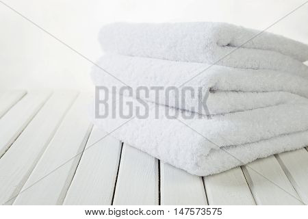 Stack of three white fluffy bath towels on the background of white boards