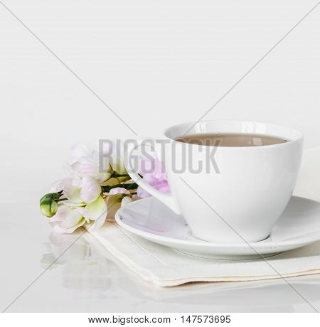 Hot tea in a white porcelain cup with saucerlinen napkin and flower in the backdrop on a white background with space for text