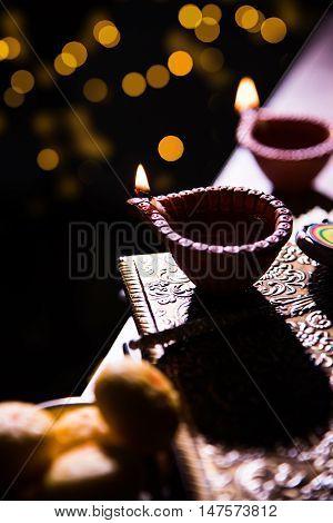 beautiful diwali diya with fire crackers and sweet pera, selective focus