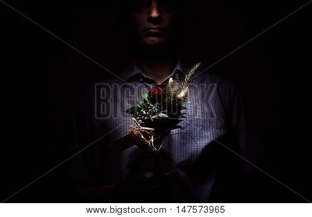 Lonely man with flowers in dark ambient, looks like desperate man.
