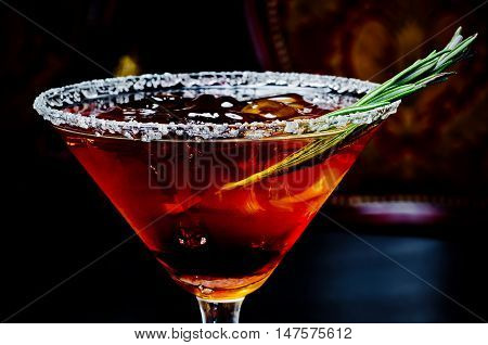 beautiful cold alcoholic cocktail on the rocks with a sprig of rosemary for menus in bars restaurants clubs
