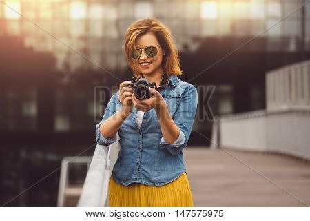 Woman photographer traveling trip photography concept. Red haired woman in casual clothing, jeans holding an amateur digital DSLR camera.