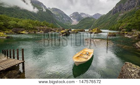 Boat in a lake close to Buerbreen Glacier Norway