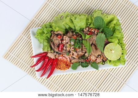 Spicy and sour mixed herb salad with pork and chicken on bamboo and white.Top view.