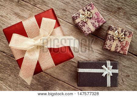 Four festive gift boxes on old wooden floor