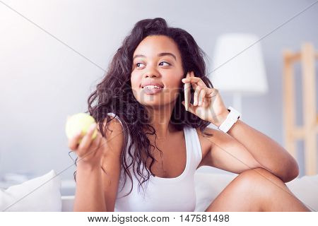 Communicative lady. Glad beautiful young woman holding tennis ball and talking on cell phone while relaxing on the couch