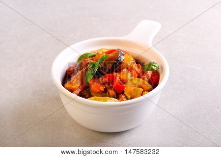 Vegetable stew in a bowl over grey background