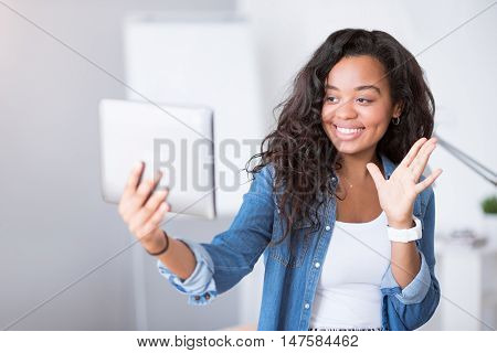 Always in touch. Positive delighted smiling woman using tablet and expressing joy while talking through the Internet