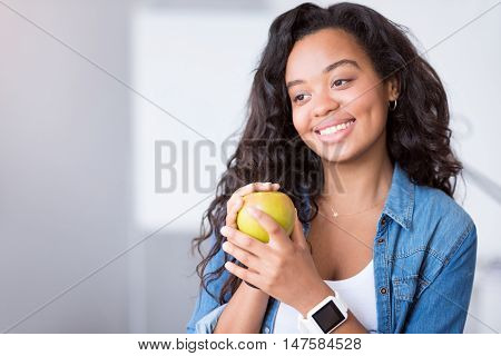 Natural present. Positive beautiful woman holding an apple and expressing joy while smiling