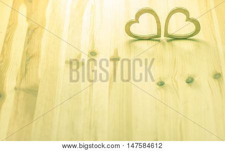 Wooden shaped hearts - Two hearts hand carved from wood in a warm light on a wooden background