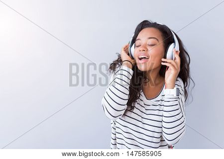 Feel the beat. Joyful delighted smiling woman wearing headphones and listening to music while standing isolated on grey background