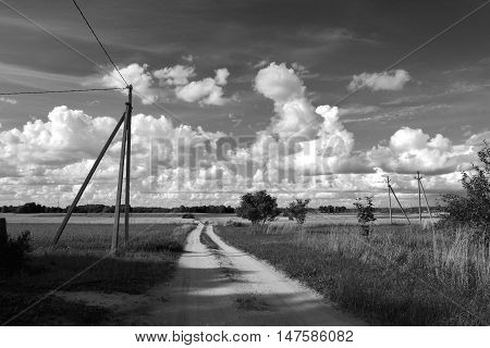 Black and white photo of summer countryside landscape with clouds and road