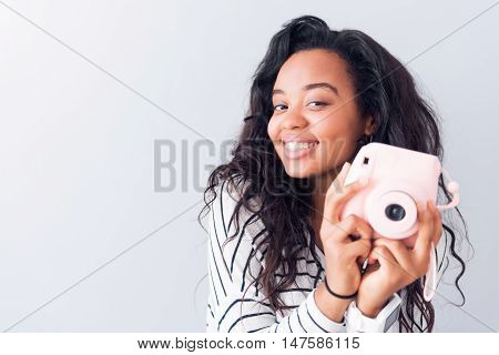My hobby. Portrait of positive delighted woman smiling and holding photo camera while standing isolated on grey background