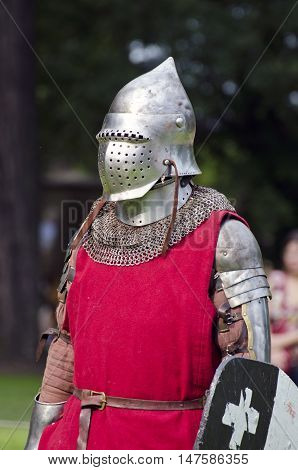 Knight actor with red clothes and armor and shield in medieval festival in town